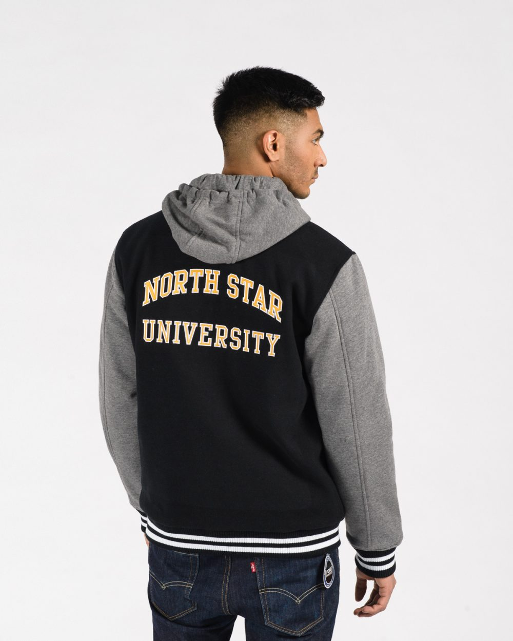 Insulated Letterman Jacket 518 Black with Charcoal sleeves on male model back view.